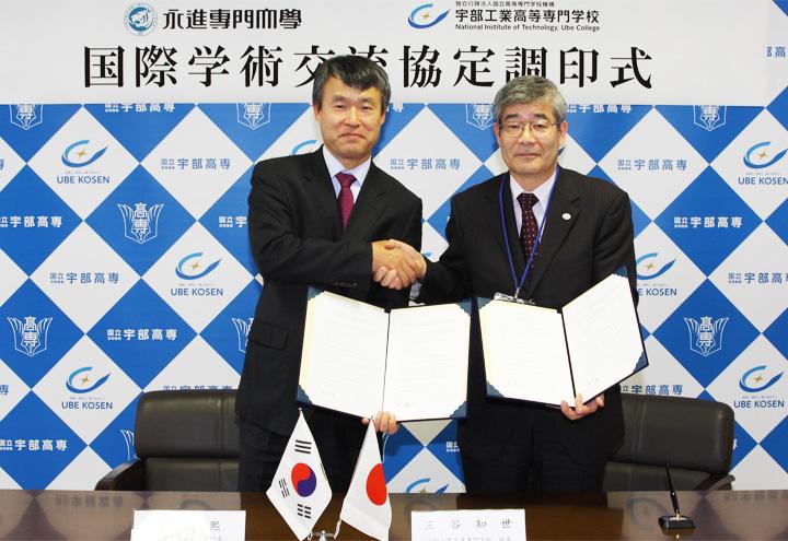 協定書を手に握手を交わす柳副学長と三谷校長