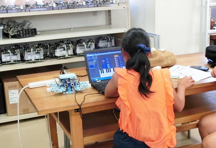 組み立てたロボットにプログラミングを行う受講者